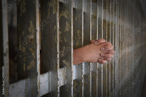 Photo  Hands of Prisoner Coming from Cell