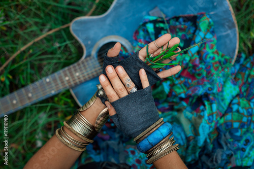 Photo  close up photo of gypsy girl hands with guitar on green grass