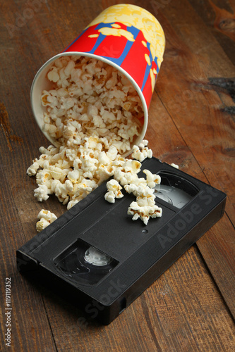 Fotografija  Popcorn near a videotape on wooden background