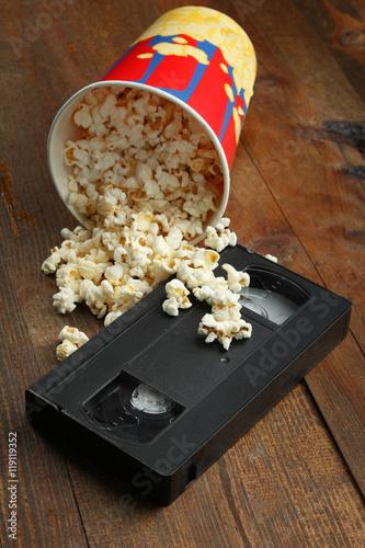 Fényképezés  Popcorn near a videotape on wooden background