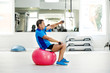 Senior man exercising with dumbbells on fitness ball in gym