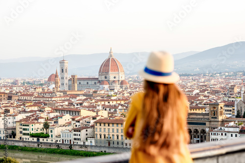 Obraz Young female tourist looking on the old town of Florence from Michelangelo square in the morning in Italy. Back focus - fototapety do salonu