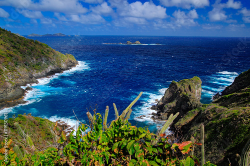 Little Tobago Island. Beautiful Caribbean sea coast landscape with ocean and dark sky with white clouds. Dark blue sea with waves. Coastline with cliff and rough sea, Trinidad and Tobago.
