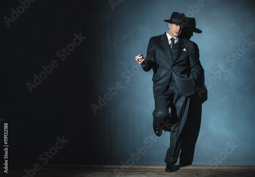 Fotografia  Retro 1940 film noir gangster wearing suit and hat. Smoking ciga