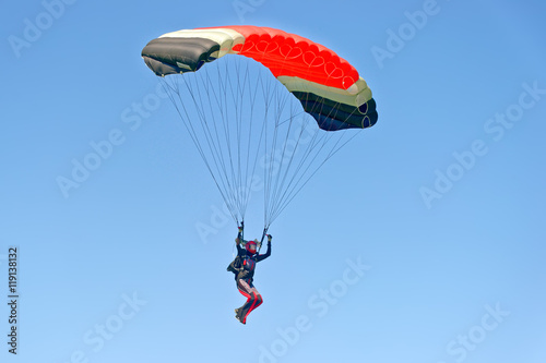 Fotografie, Obraz  Paraglider flying on colorful parachute in blue clear sky at a bright sunny summer day