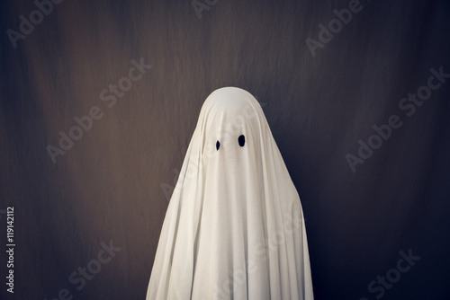 Photo  White Ghost on a gray background. Halloween holiday