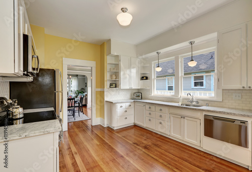 Kitchen Interior With White Cabinets Yellow Walls And Wood Floor