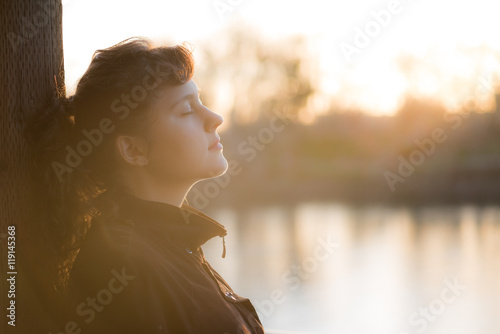Foto  Side profile of peaceful nirvana young woman in coat with closed eyes by lake wi