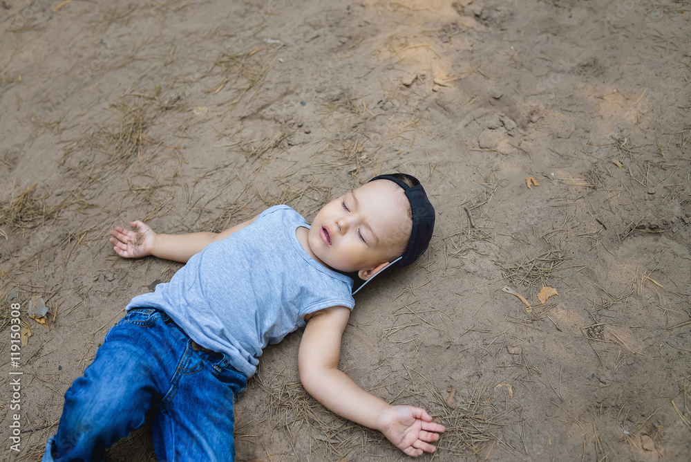 Fototapety, obrazy: Little boy laying on ground pretending sleep or unconscious
