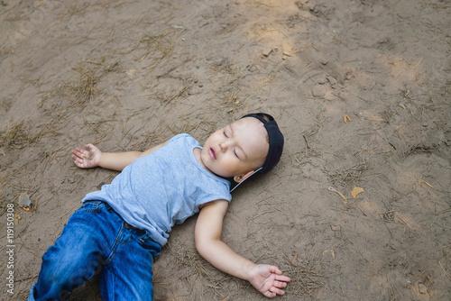 Obraz Little boy laying on ground pretending sleep or unconscious - fototapety do salonu