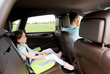 family with child in safety seat driving car