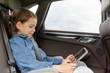 happy little girl with tablet pc driving in car