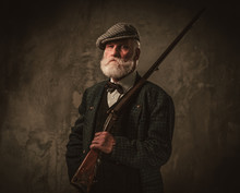 Senior Hunter With A Shotgun In A Traditional Shooting Clothing, Posing On A Dark Background.