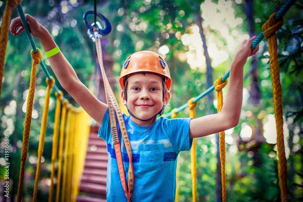 Fototapeta happy boy on the zip line. proud of his courage the child in the high wire park