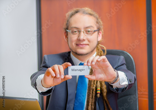 Fototapeta  Handsome man with dreads, glasses and business suit sitting by desk holding up a