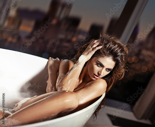 Photo  Beautiful young woman taking a bath in the bathtub
