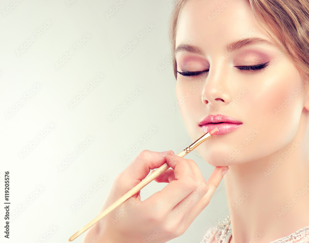 Poster  Hand of make-up master, painting lips of young beautiful model