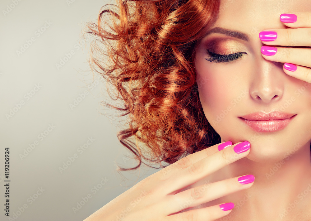 Fototapeta Beautiful model girl with curly red hair . Magenta color  manicure on nails .