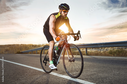 Handsome young man cycling on the road. Fototapeta