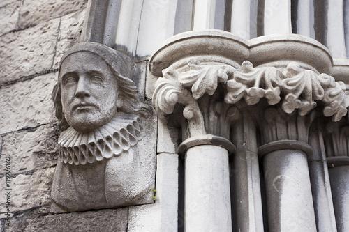 Stampa su Tela  Statue of Arlechinno on a building in Dublin