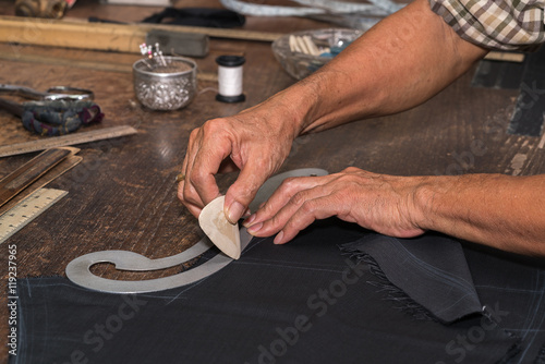 Aluminium Prints Mills Tailor at work, drawing line on fabric with chalk