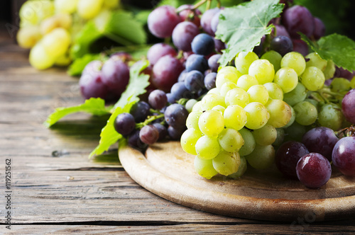 Fotografiet  Black and yellow grape on the wooden table