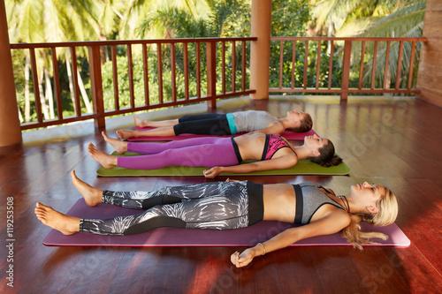 Leinwand Poster  Yoga class with women lying on floor , Savasana