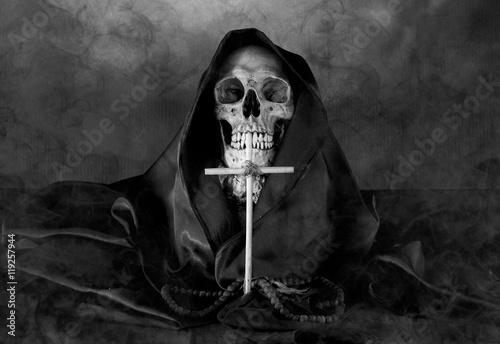 Photo  Skull and hood with Christian crucifix in dark Halloween Night (