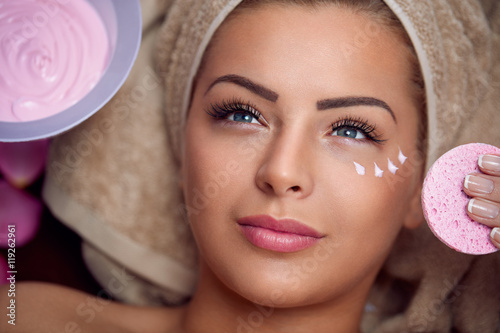 Pretty young woman with facial mask Poster
