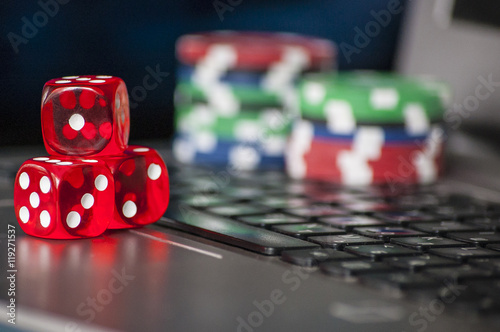 фотография  Gambling chips and red dice on laptop keyboard background