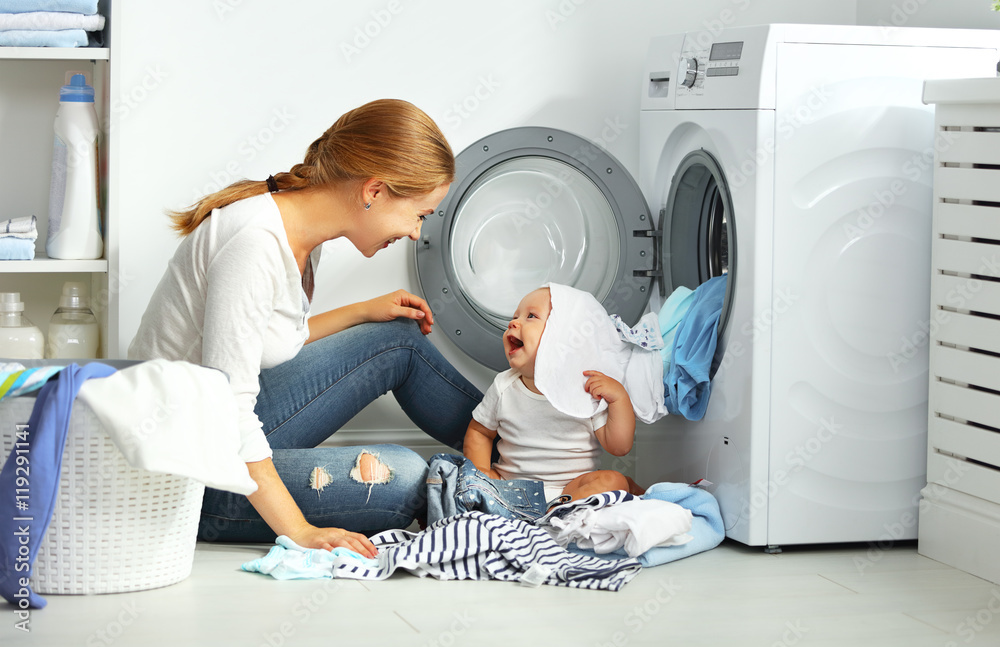 Photo  mother a housewife with a baby  fold clothes into the washing ma