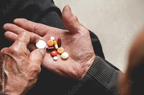 Fotografia  Many multi-colored pills in a Senior's hands