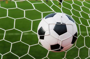 NaklejkaSoccer football in Goal net with green grass field.