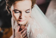 Portrait of beautiful bride with fashion veil posing on bed at wedding morning. Makeup. Brunette girl with long wavy hair styling. Wedding dress.