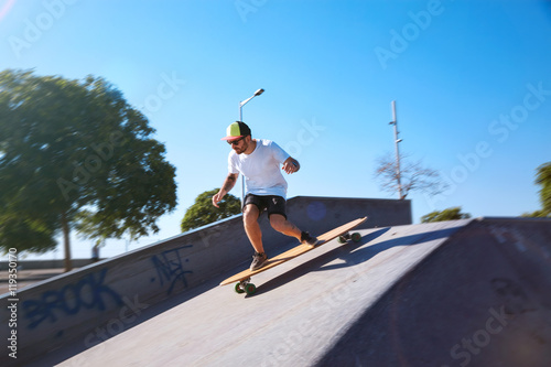 Photo  Young longboarder in plain white shirt, shorts, sneakers, baseball hat and sungl
