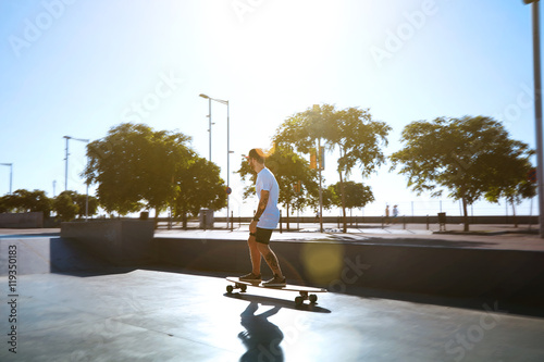 Bearded and tattooed ongboarder in a sunlit skate park skating away shot from th Canvas Print