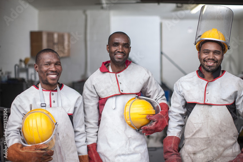 Portrait of three smiling workers with safety helmets