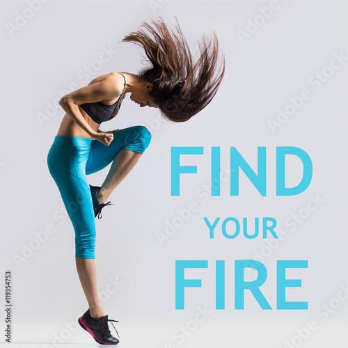 """Piękni potomstwa dopasowywają nowożytnej tancerz damy rozgrzewkowej błękitnej sportswear damy, pracujący out, taniec z jej długie włosy lataniem, pełna długość, pracowniany wizerunek na szarym tle. Fraza motywacyjna """"Znajdź swój ogień"""""""