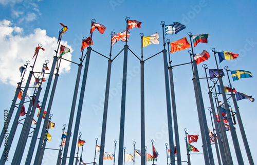 flags on background of blue sky with clouds Canvas Print
