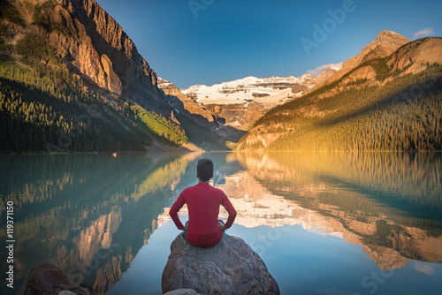 Papiers peints Canada Man sit on rock watching Lake Louise reflections