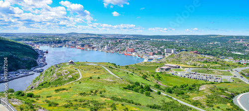 Fototapeta Panoramic views with bight blue summer day sky with puffy clouds over the harbour and city of St