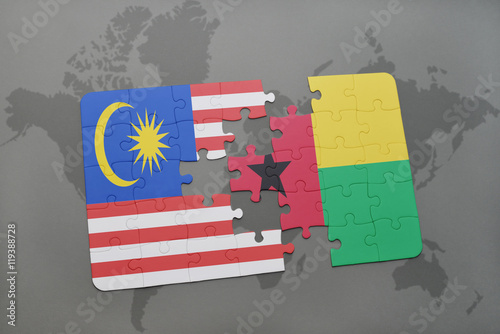Photo  puzzle with the national flag of malaysia and guinea bissau on a world map background