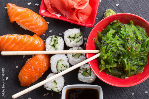 sushi and rolls with red and sauce on a slate table - 119391515