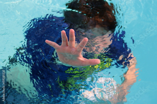 Fotografija Boy drowning in pool reaches out with hand.