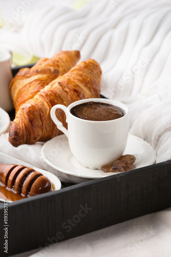 Fototapety, obrazy: Morning breakfast in bed with cup of coffee, croissants and honey on wooden tray, selective focus