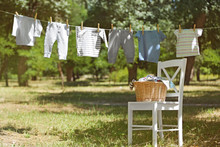 Wicker Basket On White Chair And Baby Laundry Hanging On Clothesline