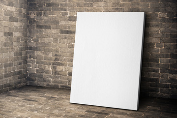 Blank white canvas frame leaning at grunge brick room, Mock up t