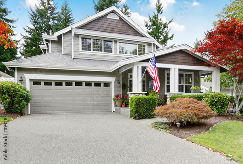 Photo Nice curb appeal of grey house with covered porch and garage