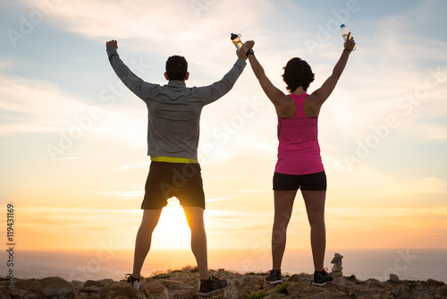 Fotografía  Sporty runner couple rising arms in victory sign after successful training outdoor on the coast facing the sun showing back