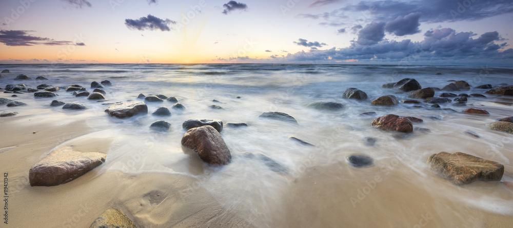Fototapeta Zachód słońca nad bałtycką plażą,głazy piastowskie na wyspie Wolin